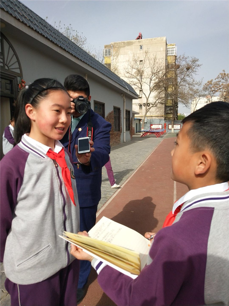 人民小記者采訪參加活動的少先隊大隊委員.jpg